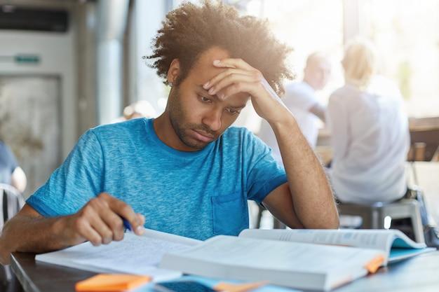 Leren en opvoeden. indoor portret van gefocuste hardwerkende afro-amerikaanse middelbare school afgestudeerde die zich voorbereidt op toelatingsexamens voor de universiteit en inschrijvingstest, notities uit leerboek schrijft