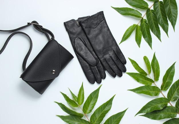 Leren heuptas, handschoenen op witte achtergrond met groene tropische bladeren. bovenaanzicht
