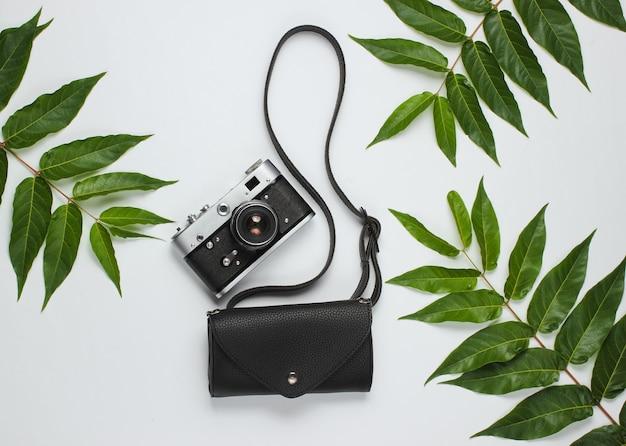 Leren heuptas, retro camera op witte achtergrond met groene tropische bladeren. bovenaanzicht