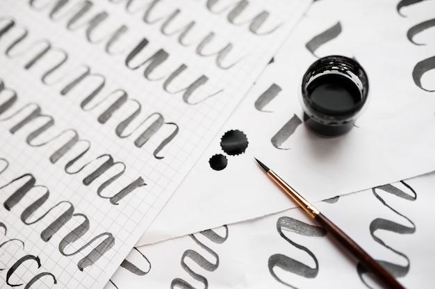 Leren kalligrafie - papier met voorbeeld en penseel en inkt