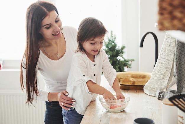Leren koken. gelukkige dochter en moeder bereiden samen bakkerijproducten. kleine helper in de keuken.