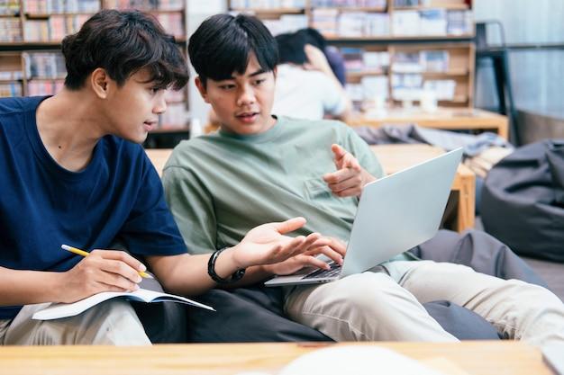 Leren, onderwijs en schoolconcept. jonge vrouw en man die voor een test of een examen studeren. bijlesboeken met vrienden. jonge studentencampus helpt vriend bij te praten en te leren.