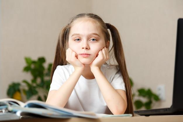 Leren op afstand of op afstand. leerling wil slapen. moe schoolmeisje met hand op gezicht zittend op laptop. online school.