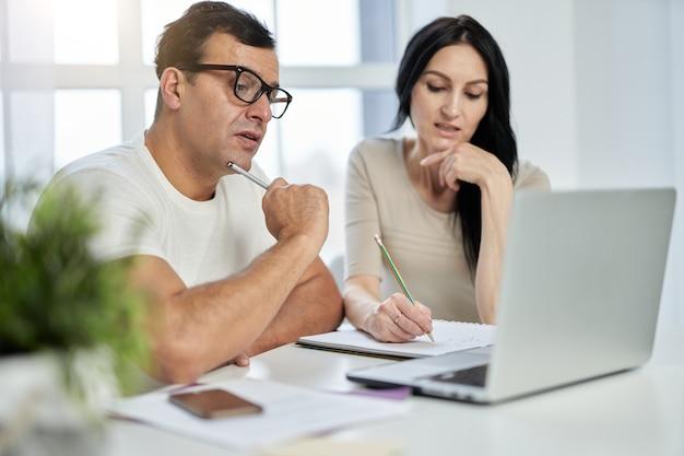 Leren op je eigen gemak. latijns-echtpaar van middelbare leeftijd, man en vrouw die aantekeningen maken tijdens online training terwijl ze op afstand studeren, met behulp van laptop thuis
