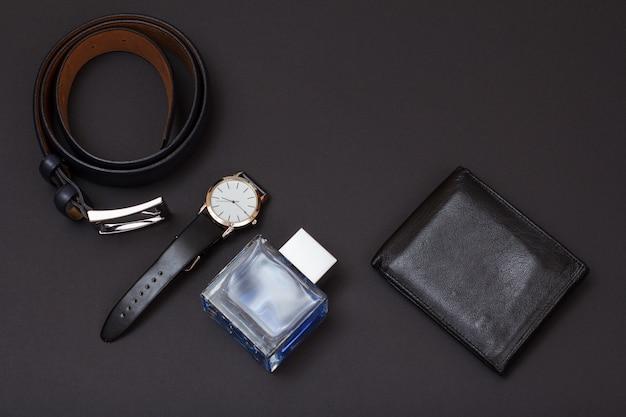 Leren riem met metalen gesp, horloge met een zwarte leren band, cologne voor heren en portemonnee op zwarte achtergrond. accessoires voor heren. bovenaanzicht.