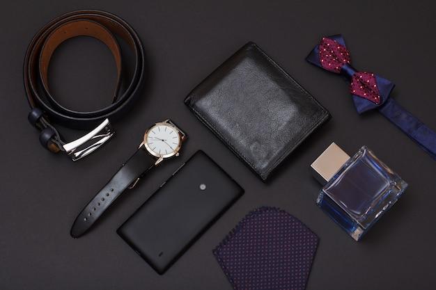 Leren riem met metalen gesp, horloge met een zwarte leren band, mobiele telefoon, keulen voor mannen, portemonnee en zakdoek op zwarte achtergrond. accessoires voor heren.