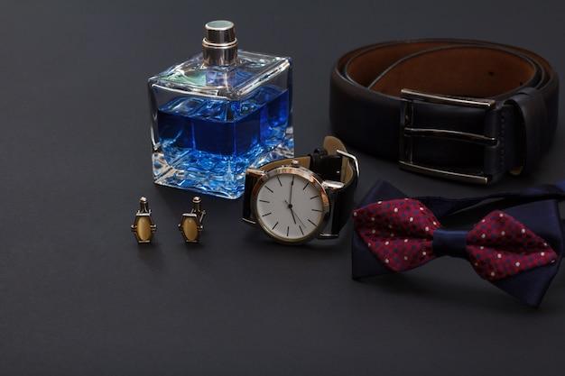 Leren riem met metalen gesp, horloge met zwarte leren band, cologne voor heren, manchetknopen en vlinderdas op zwarte achtergrond. accessoires voor heren.