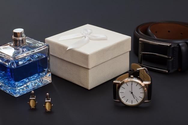 Leren riem met metalen gesp, horloge met zwarte leren band, cologne voor heren, manchetknopen en witte geschenkdoos op zwarte achtergrond. accessoires voor heren.