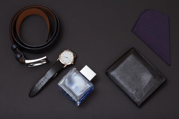 Leren riem met metalen gesp, horloge met zwarte leren band, cologne voor heren, portemonnee en zakdoek op zwarte achtergrond. accessoires voor heren.