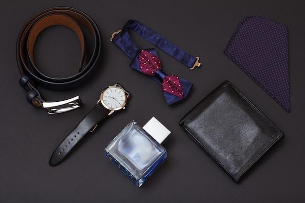 Leren riem met metalen gesp, horloge met zwarte leren band, cologne voor heren, portemonnee, vlinderdas en zakdoek op zwarte achtergrond. accessoires voor heren.