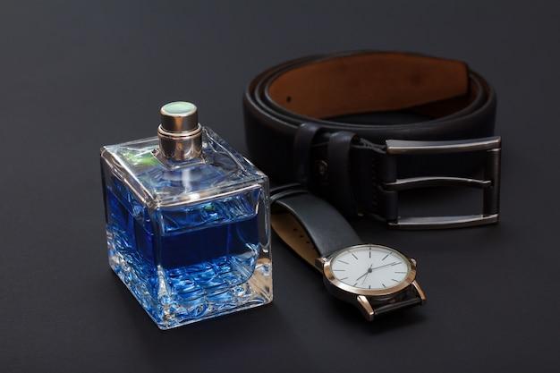 Leren riem met metalen gesp, horloge met zwarte leren band en cologne voor heren op zwarte achtergrond. accessoires voor heren.