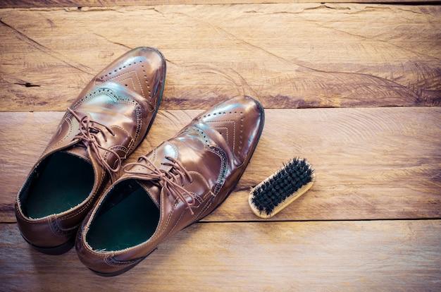 Leren schoenen, borstels, geplaatst op een houten vloer.