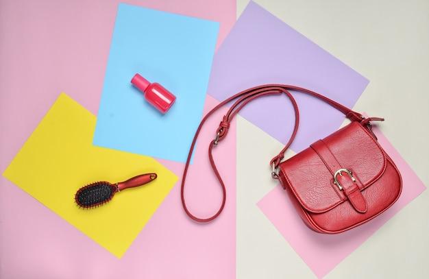Leren tas, kam, parfumfles op een gekleurd pastel oppervlak. minimalisme. bovenaanzicht