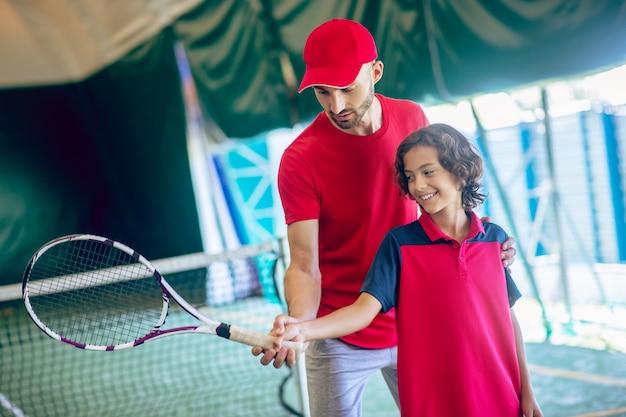 Leren tennissen. mannelijke tenniscoach in rode kleren die een jongen toont hoe hij het racket moet vasthouden