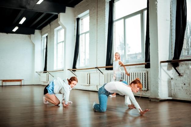 Les in de dansstudio. professionele balletleraar gekleed in een spijkerbroek en haar nieuwe dans leren