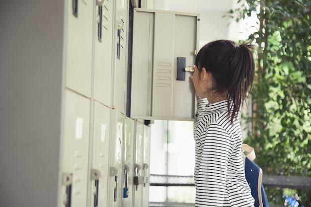 Les voorbereiden. klein schoolmeisje dat zijn tas voor de les in een kluisje in de kleedkamer stopt.