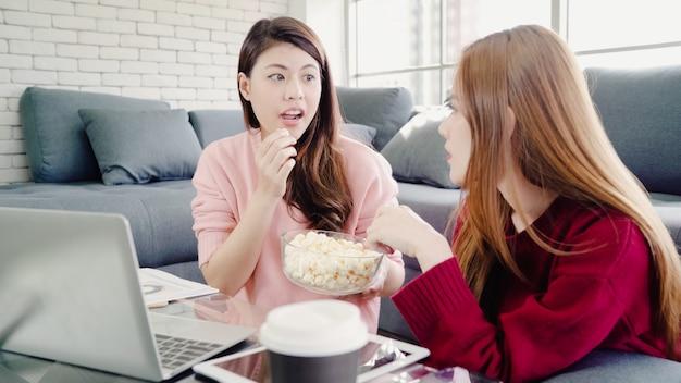 Lesbisch aziatisch paar dat laptop met behulp van die begroting in woonkamer thuis maken