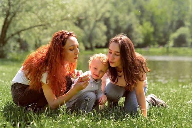 Lesbisch koppel brengt tijd door met hun kind in het park