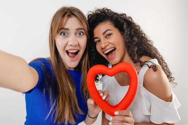 Lesbisch koppel dat selfie met rood hartvormig cijfer geïsoleerd maakt