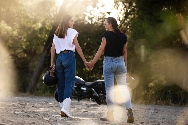 Lesbisch koppel hand in hand in de buurt van motorfiets tijdens een roadtrip
