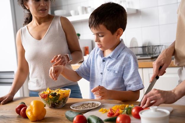 Lesbisch koppel met hun zoon die wat eten klaarmaakt