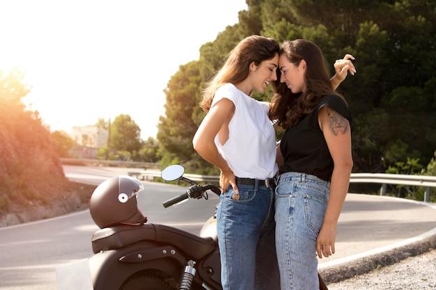 Lesbisch koppel omarmen in de buurt van motorfiets tijdens een road trip