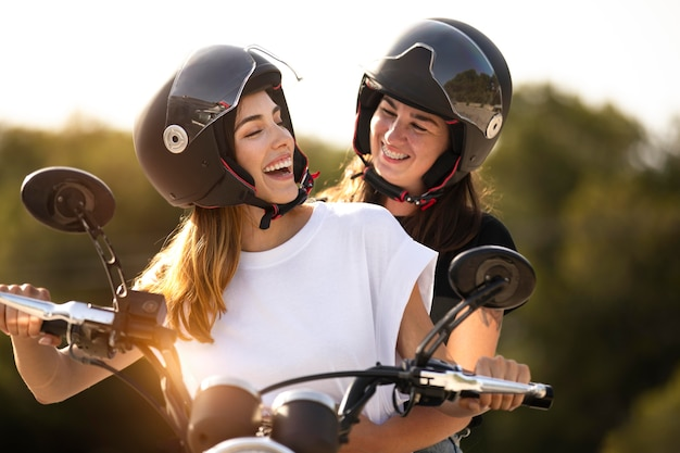 Lesbisch koppel op een motorfiets met helmen op