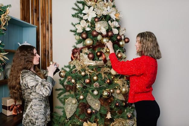 Lesbisch koppel samen binnenshuis vrolijk communiceren, voorbereiding voor de viering van kerstmis.