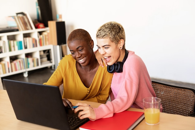Lesbisch lachend koppel met laptop op tafel thuis
