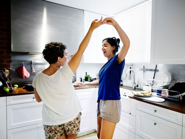 Lesbisch paar dat in de keuken danst