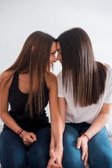 Lesbisch paar dat terwijl leunende voorhoofden zit