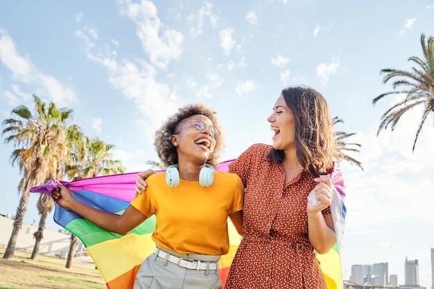 Lesbisch verliefde paar kijken elkaar aan met regenboogvlag concept van trots homoseksuele gelijkheid f...