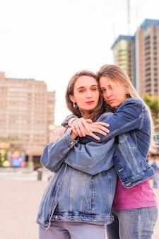 Lesbische jonge multi-etnische paar knuffelen op een zonlicht zonsopgang samen geluk vriendinnen