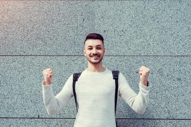 Lessen geannuleerd. gelukkige arabische student buiten. succesvolle en zelfverzekerde jonge man stak zijn hand op