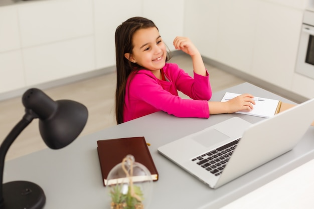 Lessen op afstand. het kind lacht vrolijk en krijgt kennis op afstand. klein meisje studeert online leren vanuit huis met laptop. onlineschool.