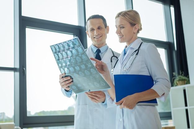 Let hier op. positief opgetogen intelligente vrouw die samen met haar collega staat en naar de röntgenscan wijst terwijl ze een diagnose met hem bespreekt