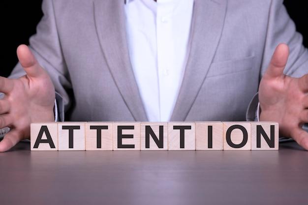Let op, het woord is geschreven op houten kubussen, blokken op de achtergrond van een man