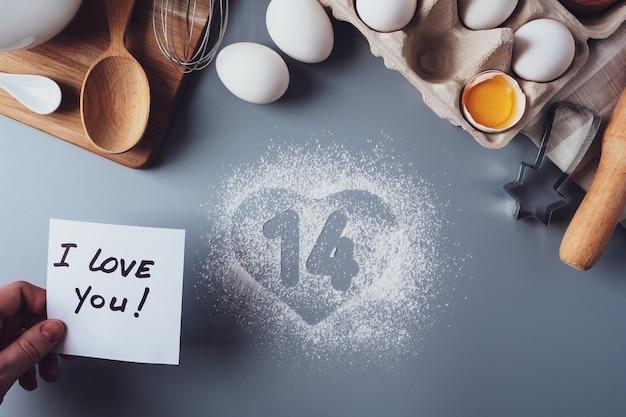 Let op ik hou van jou, de cijfers 14 en een hart van meel. het concept van valentijnsdag. zelfgemaakte koekjes maken voor valentijnsdag, plat, bovenaanzicht. ingrediënten voor het bakken op een grijze achtergrond.