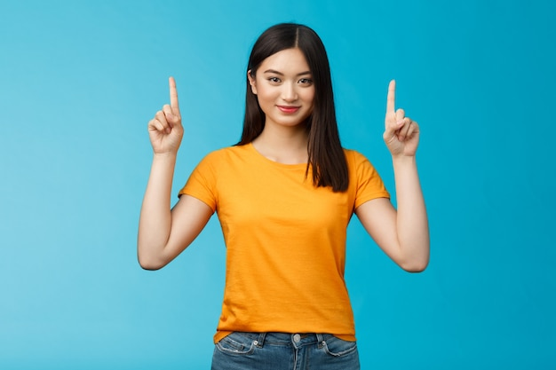 Let op, zie geweldige promo. assertieve, knappe, zelfverzekerde aziatische vrouw die reclame voor vrienden toont, wijsvingers opsteekt die naar boven wijzen, zelfverzekerde glimlachende camera, blauwe achtergrond vastbesloten.