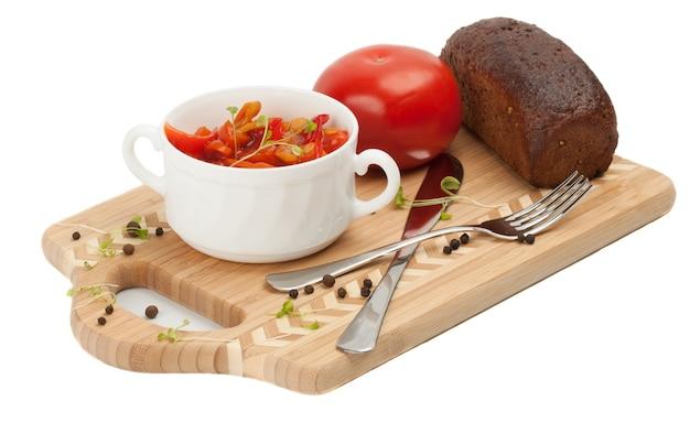 Letcho, tomaten en zwart brood op een snijplank. op een witte achtergrond.