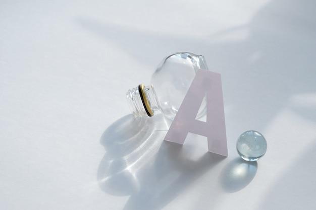 Letter a, met knikkers en glazen pot in witte tafel