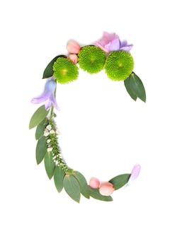 Letter c gemaakt van bloemen en kruiden op witte achtergrond