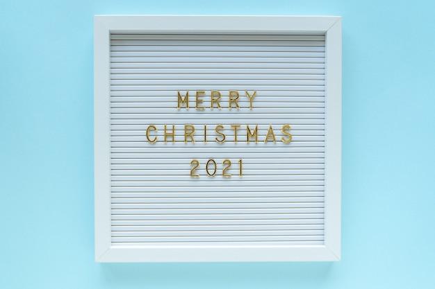 Letterbord met merry christmas 2021-groet, decoraties op blauwe pastel achtergrond. kerst samenstelling. bovenaanzicht