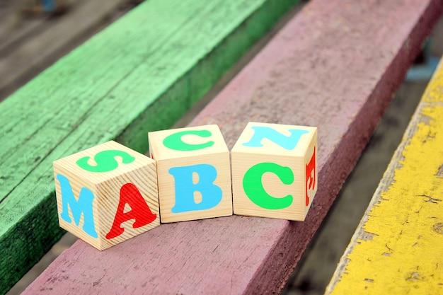 Letters van het engelse alfabet op houten speelgoedblokken die op de oude planken staan