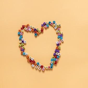 Lettervormige kralen de hobby's van veel mensen staan op een hartvormige gele achtergrond.