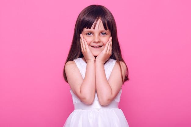 Leuk, aangenaam uitziend klein meisje dat een stijlvolle witte jurk draagt die naar voren kijkt met een charmante, gelukkige uitdrukking, tevreden is, iets bewondert, geïsoleerd over roze muur