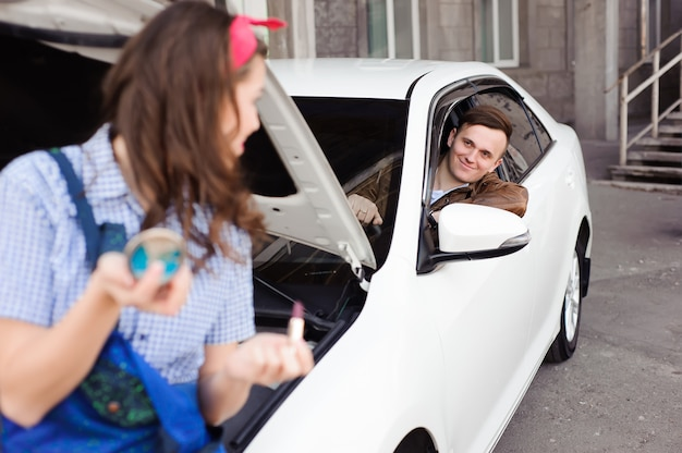 Leuk aantrekkelijk meisje die motor van een auto onderzoeken bij de autoreparatiewerkplaats.