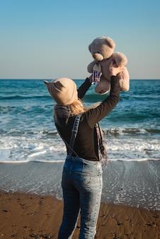 Leuk aardig meisje met een teddybeer in haar handen die op de kust lopen walking