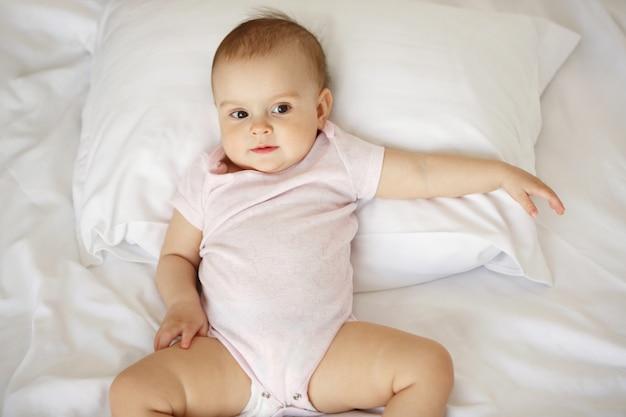 Leuk aardig portret van weinig babyvrouw die op hoofdkussen in bed liggen. van boven.