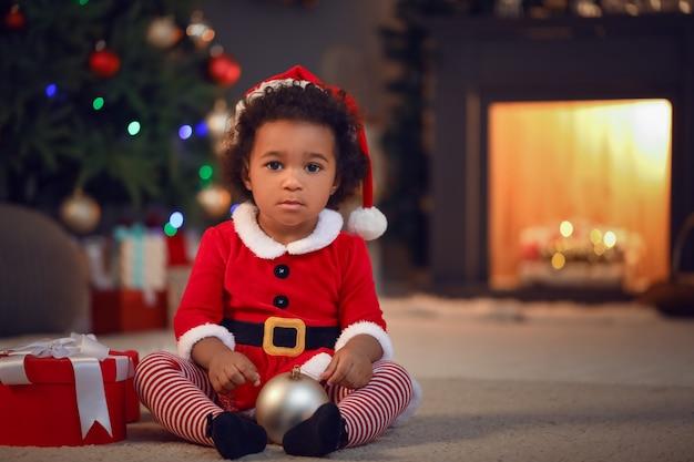 Leuk afrikaans-amerikaans babymeisje thuis op kerstavond